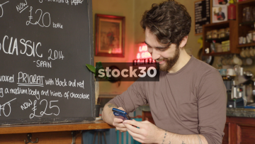Man In Coffee Shop Smiling While Using Smart Phone