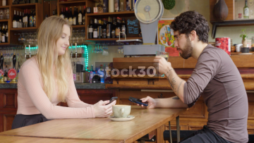 Young Couple In Bar Chatting While Using Smart Phones