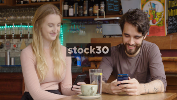 Happy Young Couple In Bar Chatting While Looking At Photos On Smart Phone