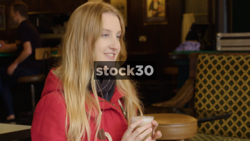 Young Woman Drinking Coffee In Coffee Shop While Chatting