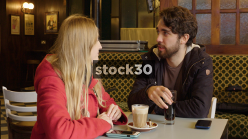 Happy Young Couple In Coffee Shop Having Animated Conversation