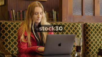Young Woman Using Apple MacBook Pro Laptop In Coffee Shop