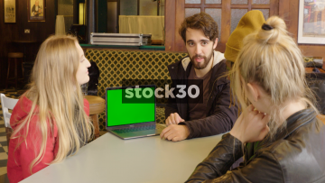 Group Of Young Friends Having Meeting While Looking At Information On Apple MacBook Pro Laptop, Green Screen