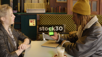 Two Friends Laughing And Chatting In Coffee Shop While Looking At Photos On Smart Phone, Green Screen