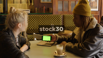 Two Friends In Coffee Shop Chatting And Looking At Information On Smart Phone