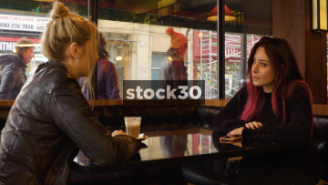 Two Young Women Chatting At Table In Coffee Shop