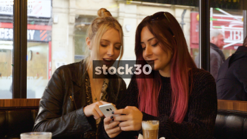 Two Women Laughing And Chatting In Coffee Shop While Looking At Photos On Smart Phone