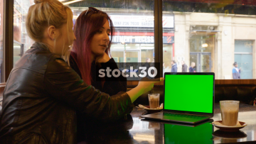 Two Young Women Looking At Information On Apple MacBook Pro Laptop In Coffee Shop