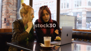 Two Young Women In Coffee Shop Chatting While Using Apple MacBook Pro Laptop