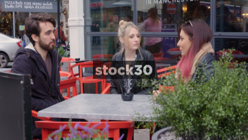 Three Young Friends having Conversation At Table Outside Bar