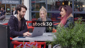 Three Young Friends Discussing Business Idea While Looking At Apple MacBook Pro Laptop