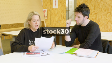 Man And Woman In Creative Meeting Discussing Potential Designs - Wide Shot