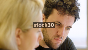 Man And Woman In Creative Meeting Discussing Potential Designs - Man Not Convinced