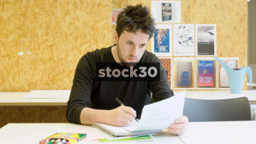 Man Studying Or Revising And Writing On Notepad - Wide Shot