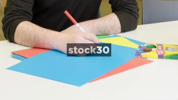 Man Doodling On Blue Paper With Felt Tip Pen