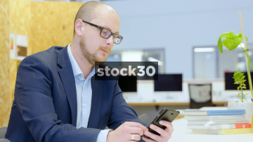 Business Man In Office Receives Call On Smart Phone