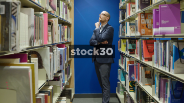 Man In Library Selecting Books From Shelf