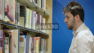 Man In Library Selecting And Looking Through Books
