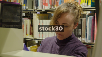 Woman Browsing Library Books, Viewed Through Bookshelf