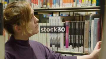 Woman In Library Contemplating And Looking Through Books