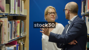 Librarian Making Recommendations To Man In Library