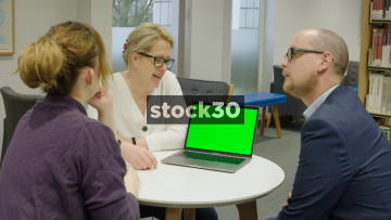 3 Colleagues Around Laptop In Library, Woman Explaining Something, Animated Chat, Green Screen