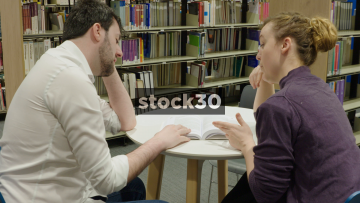 Woman Helping Man Study In Library, Wide Shot Then Close Up On Book