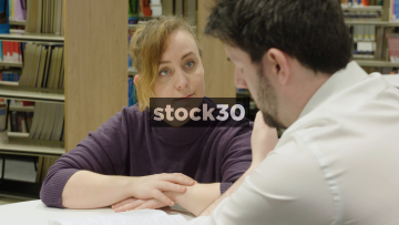 Man And Woman Having Conversation In Library While Studying