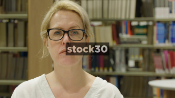 Close Up Slow Motion Shot Of Woman Looking To Camera In Library, Neutral Expression