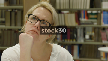 Close Up Slow Motion Shot Of Woman In Library Contemplating, Thinking