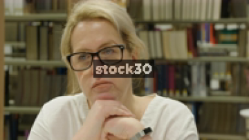 Close Up Slow Motion Shot Of Woman In Library Contemplating And Looking Upset Or Sad