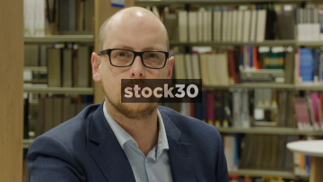 Close Up Slow Motion Shot Of Man Looking To Camera In Library, Neutral Expression