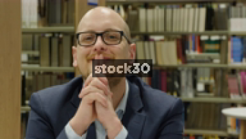 Close Up Slow Motion Shot Of Man Looking To Camera In Library, Smiling