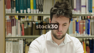 Close Up Slow Motion Shot Of Man Looking To Camera And Smiling In Library
