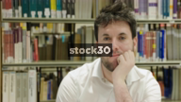 Close Up Slow Motion Shot Of Man In Library Looking To Camera, Contemplating