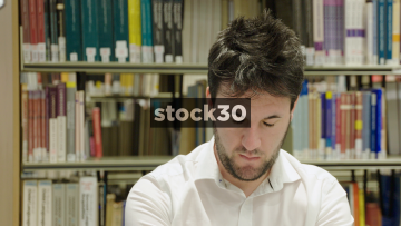 Close Up Slow Motion Shot Of Man In Library Pulling Silly Face
