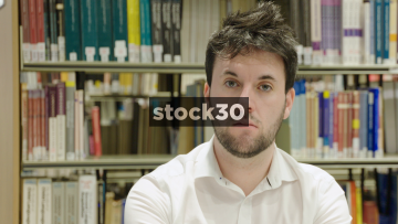Close Up Shot Of Man In Library Pulling Silly Face