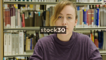 Close Up Slow Motion Shot Of Woman Looking To Camera In Library With Neutral Expression
