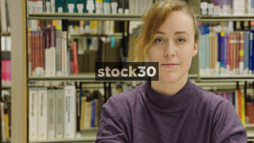 Close Up Slow Motion Shot Of Woman Looking To Camera In Library And Smiling
