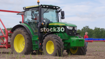 Farmer Driving Tractor While Workers Harvest Asparagus