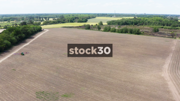 High Drone Shot Of Large Farm Field And Tractor, UK