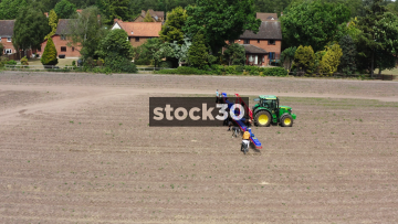 Drone Shot Orbiting Around Farm Workers And Tractor In Field, UK