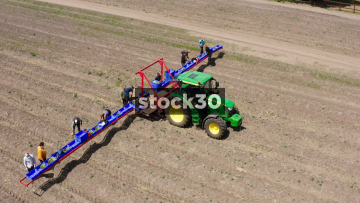 Drone Shot Orbiting Around Farm Workers And Tractor In Field, Close Up, UK