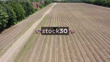 Drone Flyover Shot Of Farm Workers Loading Asparagus Onto Tractor, UK