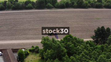 Orbiting Wide Drone Shot Of Farm Workers And tractor Harvesting Asparagus In Field, UK