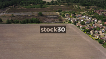 Wide Drone Shot Of Farm Field With Farm Workers And Tractor Harvesting Asparagus, UK