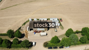 Orbiting Drone Shot Of Farm Warehouse And Workers Caravans, UK