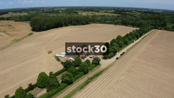 Drone Flyover Shot Of Farm Buildings And Field With Vehicles, UK