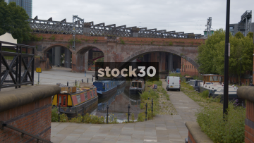 Railway Viaduct Bridge Over The Bridgewater Canal In Castlefield With Train Passing Over, Manchester, UK