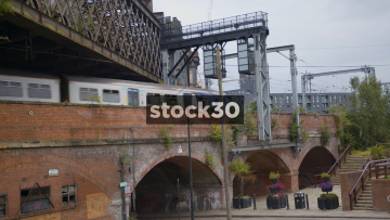 Railway Bridge In Castlefield, Manchester, WIth Train Passing Over, UK